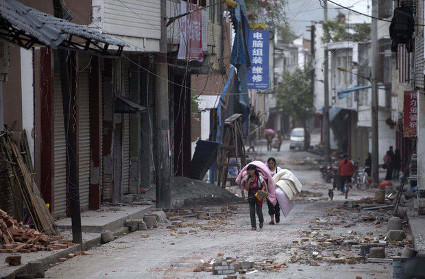 "In this photo released by China's Xinhua news agency, people carrying their belongings walk in quake-damaged Gucheng Village in southwest China's Sichuan Province after an April 2013 earthquake. Experts say Oregon is due for ""the big one"" any time now, and the state's infrastructure is inadequate to withstand such a powerful quake. (The Associated Press)"